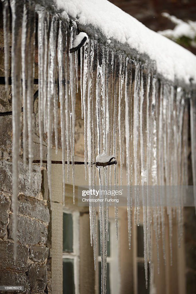 Icicles hang from the roof of a cottage in the village of Tissington, Derbyshire, on January 21, 2013 in Ashbourne, United Kingdom. The Met Office has issued a red weather warning for parts of the Uk and advising against all non-essential travel as up to 30cm of snow is expected to fall in some areas today. The adverse weather has closed nearly 5,000 schools and caused many airports to cancel flights.