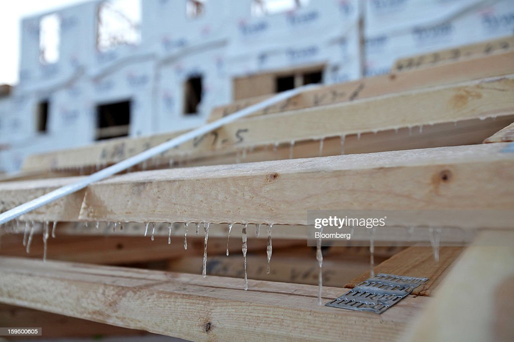 Icicles hang from trusses stacked behind new Lexington Homes LLC townhomes under construction in Des Plaines, Illinois, U.S., on Monday, Jan. 14, 2013. The U.S. Census Bureau is scheduled to release housing starts figures on Jan. 17. Photographer: Tim Boyle/Bloomberg via Getty Images