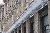 icicles on a grid under the building at winter. prevention of accident in city.