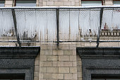 closeup of icicles on a grid under the building at winter. prevention of accident in city
