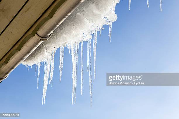 Icicles On Roof Against Clear Sky