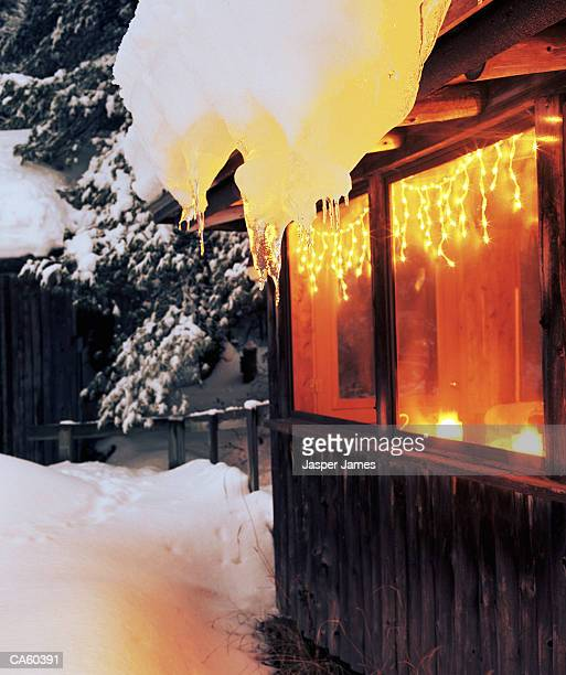 Icicles on side of cabin surrounded in snow