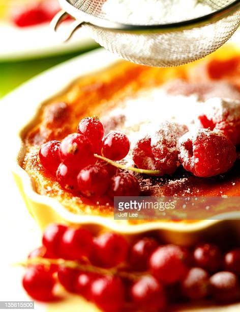 Icing sugar being sifted over fruit creme brulee