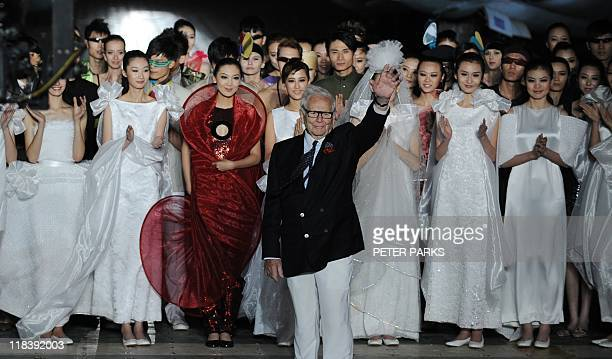 Iconic French fashion designer Pierre Cardin waves after his fashion show on board an exsoviet aircraft carrier Kiev at the Tianjin Binhai Aircraft...