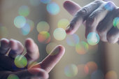 Two touching hands reach out to each other.  The background is soft pastel colours and dreamy bokeh. This is a conceptual image that could represent, religion, separation, new beginnings, ambition or
