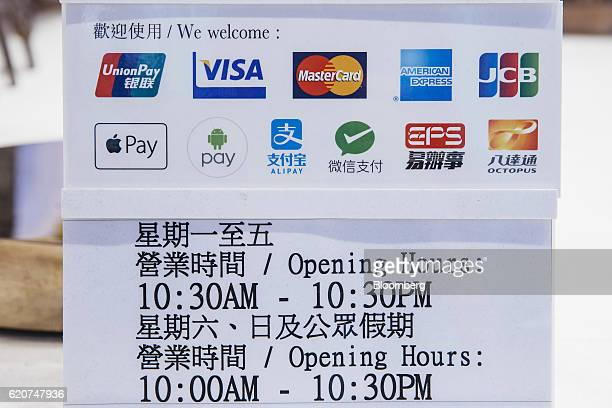 Icons for various payment services are displayed above the openinghours sign inside a Sa Sa International Holdings Ltd store in Hong Kong China on...