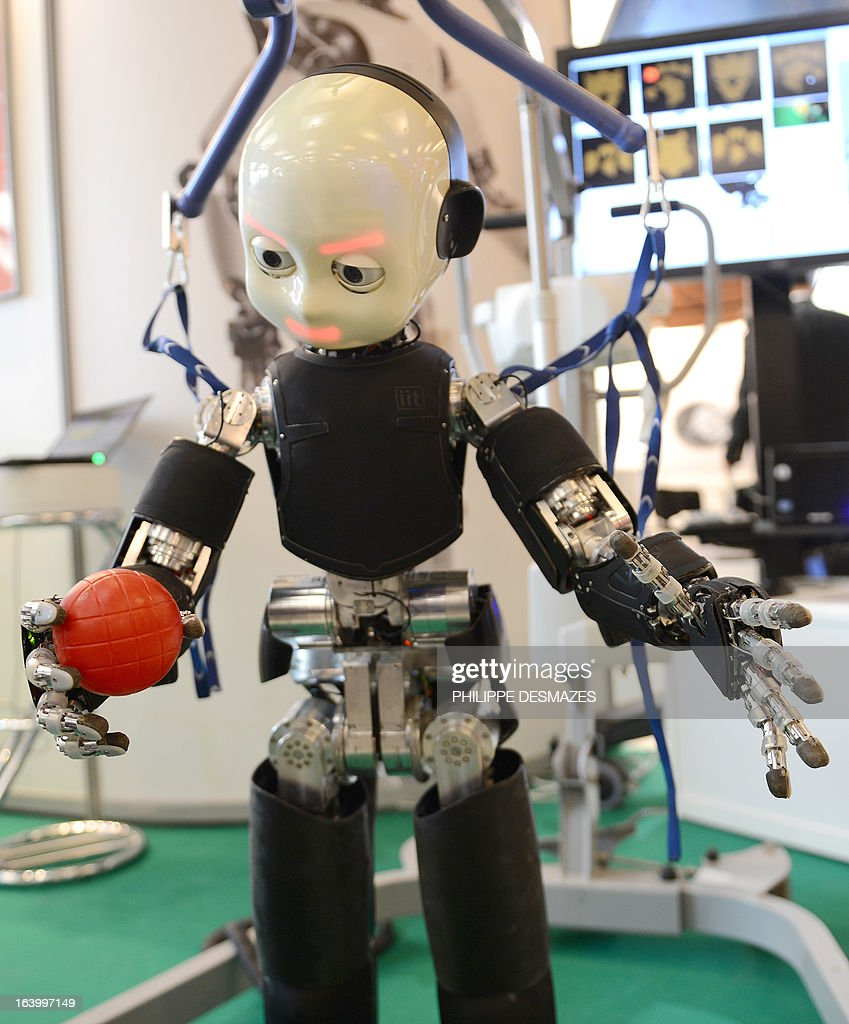 iCub, a Humanoid robot, carries a ball in its hand on March 19, 2013 at the Innorobo 2013 European summit in Lyon, southeastern France.