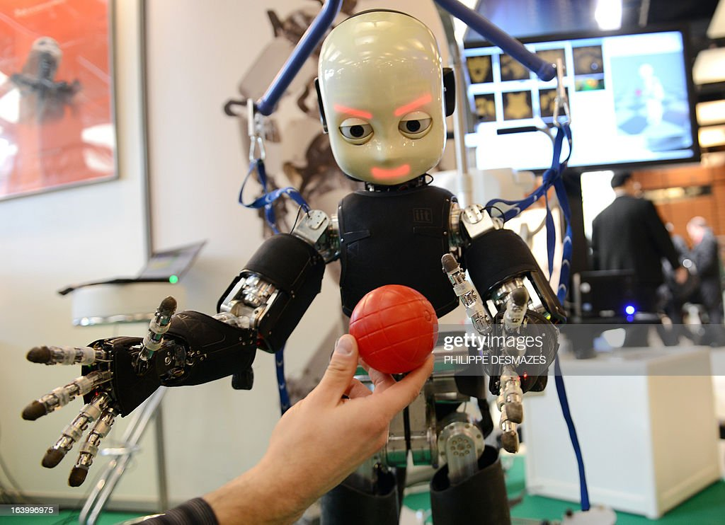 ICub, a Humanoid robot, tries to grab a ball on March 19, 2013 at the Innorobo 2013 European summit in Lyon, southeastern France.