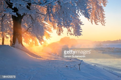 Icy river at sunset with frost smoke and trees.