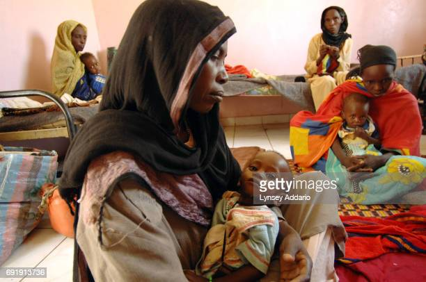 Ida Ibrahim holds her malnourished son Ahmad Saleh 13 months at a feeding center at a hospital in Bahai in northeastern Chad October 17 2006 Bahai...