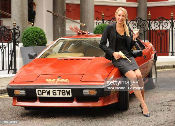 Ida Johansson with a limited edition gold plated 'golden gun' replica and the 1980 Lotus Esprit Turbo driven by Bond actor Roger Moore in the 1981...