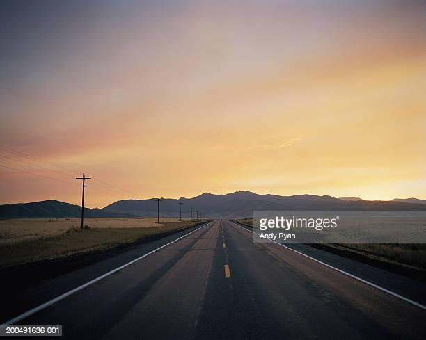USA, Idaho, straight country road at sunset