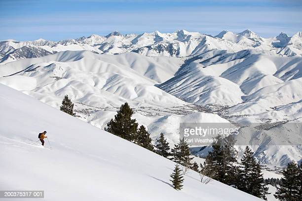 USA, Idaho, Sun Valley, man downhill skiing, side view