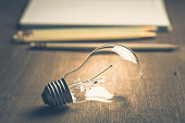 Light bulb with pencils and notebook on background