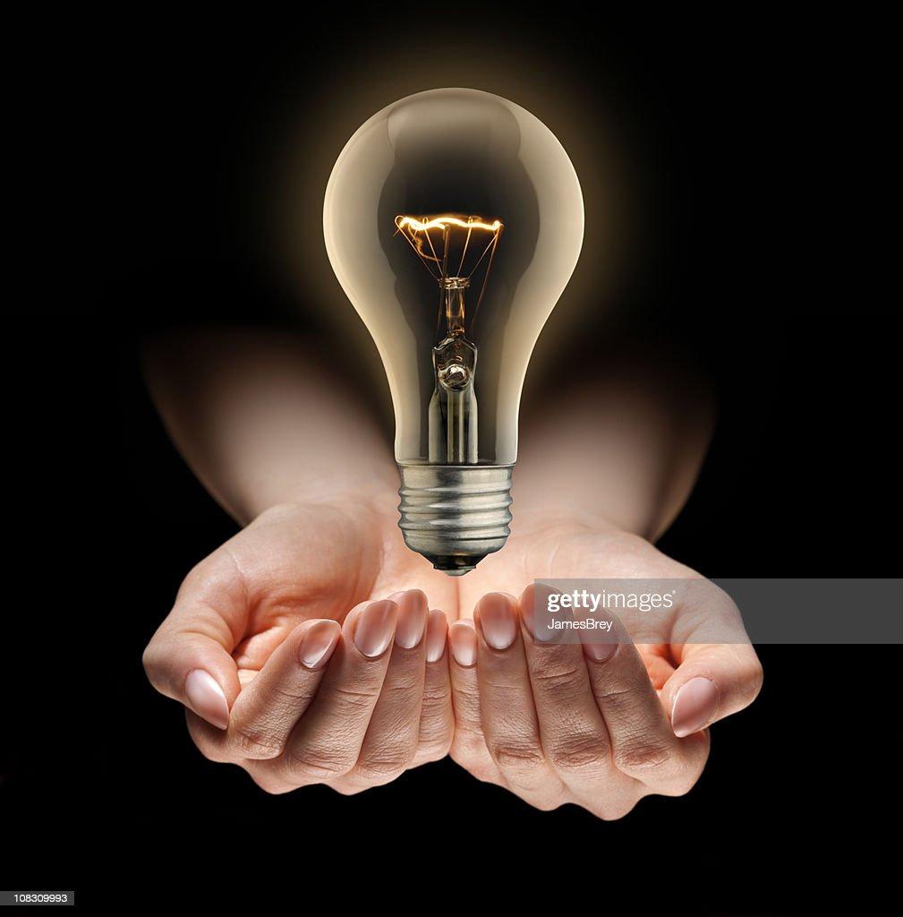 Idea Light Bulb Levitating Over Nurturing Hands : Stock Photo