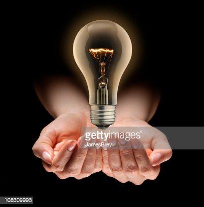 Idee Glühbirne Levitating über Pflegende Hände : Stock-Foto