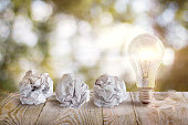 Great idea with a crumpled office paper and light bulb standing on a table on blurred background.