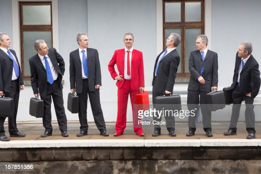 identical executives looking at one in red suit