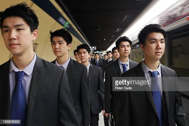 Identical men in suits walking along platform