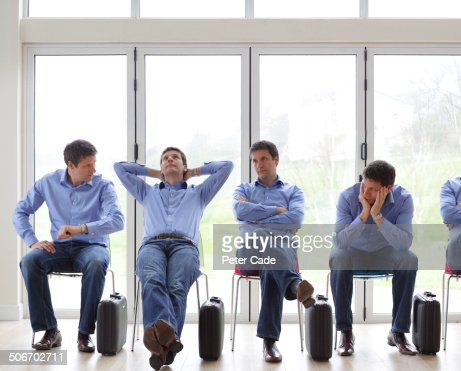 Identical men sat on chairs waiting