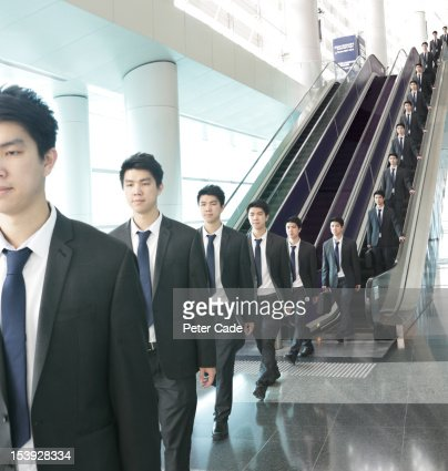 Identical men travelling down escalator : ストックフォト