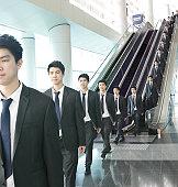 Identical men travelling down escalator