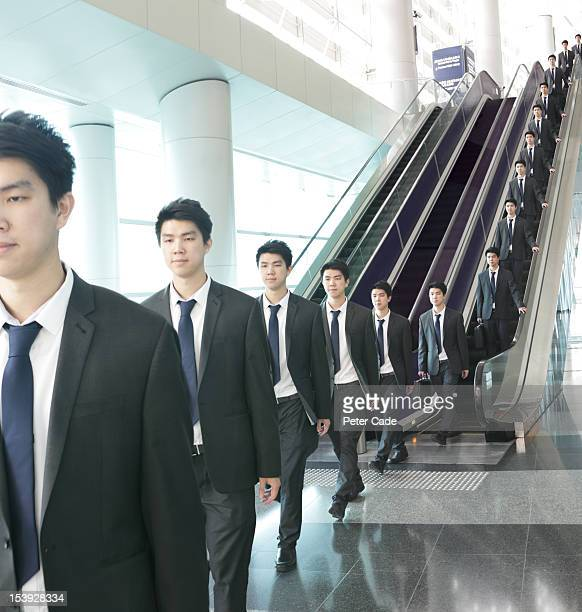 Identical men travelling down escalator