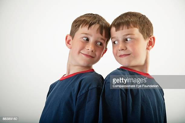 identical twin boys standing back to back