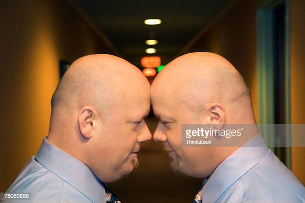 Identical twins standing face-to-face