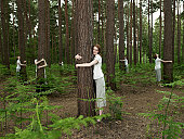 Identical women hugging trees in forest (digital composite)