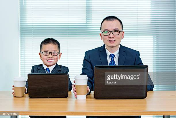 Identically dressed man and boy with matching laptops & cups