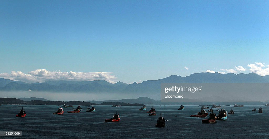 'BEST PHOTOS OF 2012' (): Idle cargo vessels wait to dock in the Guanabara Bay of Rio de Janeiro, Brazil, on Thursday, Aug. 2, 2012. Petroleo Brasileiro SA (Petrobras), the worst-performing global oil company this year, fell the most in six weeks after unexpectedly reporting its first quarterly loss in 13 years as local currency depreciation pushed up costs. Photographer: Dado Galdieri/Bloomberg via Getty Images