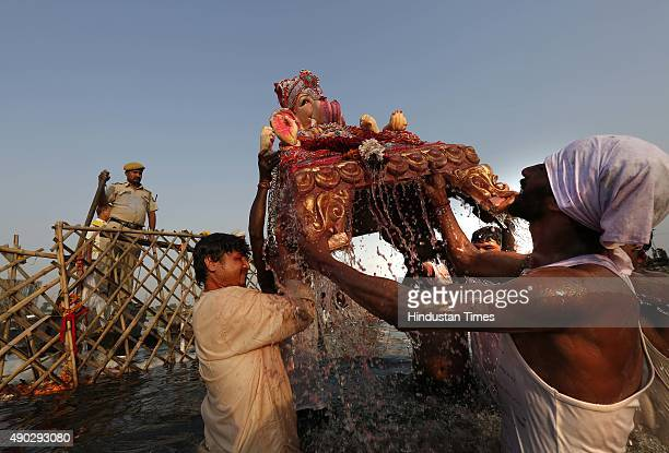 Idol of lord Ganesha being immersed in Yamuna River at Okhla on the last day of the Ganesh Chaturthi festival on September 27 2015 in New Delhi India...