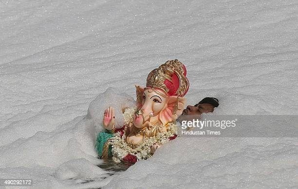 Idol of Lord Ganesha being immersed in Yamuna River on the last day of the Ganesh Chaturthi festival at Okhla on September 27 2015 in New Delhi India...