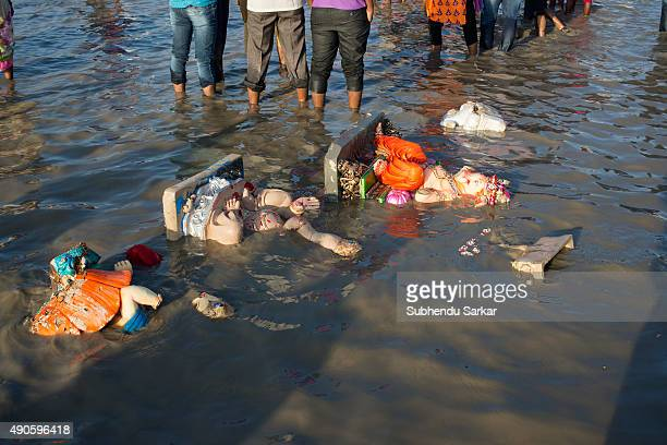 Idols of lord Ganesha are washed onto the shore after being immersed into the sea in Mumbai Ganesha Chaturthi or Ganapati festival is celebrated in...