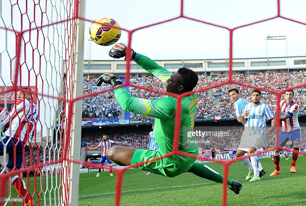 Idriss Kameni of Malaga CF fails to stop Tiago Mendes of Club Atletico de Madrid scoring his team's opening goal during the La Liga match between...