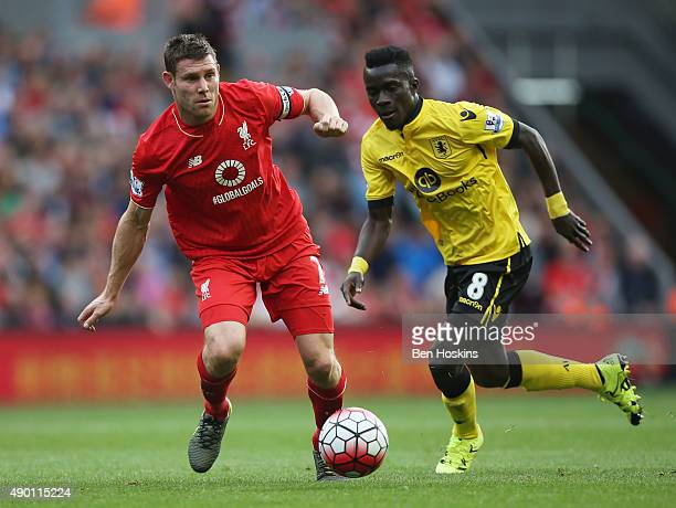 Idrissa Gueye of Aston Villa and James Milner of Liverpool compete for the ball during the Barclays Premier League match between Liverpool and Aston...