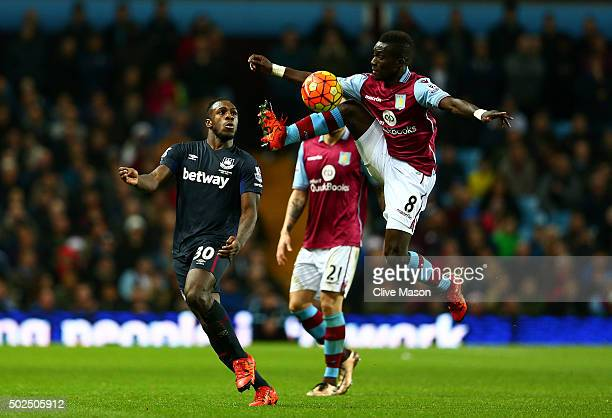 Idrissa Gueye of Aston Villa leaps to control the ball ahead of Michail Antonio of West Ham United during the Barclays Premier League match between...