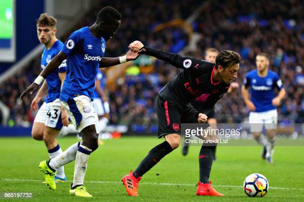 Idrissa Gueye of Everton and Mesut Ozil of Arsenal in action during the Premier League match between Everton and Arsenal at Goodison Park on October...
