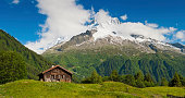 Idyllic Alpine chalet summer mountain meadow panorama Alps