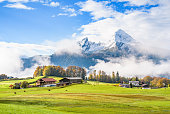 Traditional bavarian rural landscape with green meadow, farmhouses, colorful trees and the snow covered mount Watzmann