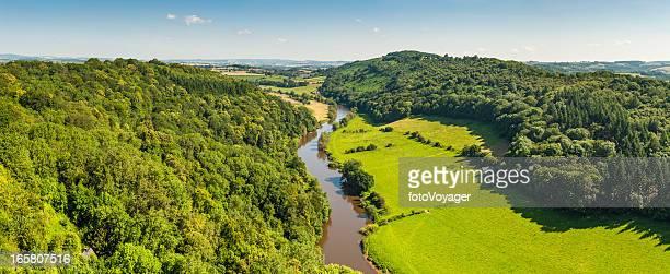 Idílico país meadering através de rio vale de Verão