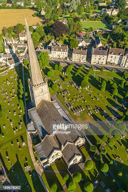 Idyllic English country churchyard Cotswold village aerial view UK