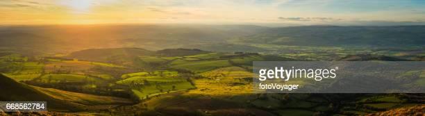 Idyllic green hills pasture mountain ridges illuminated by sunset panorama