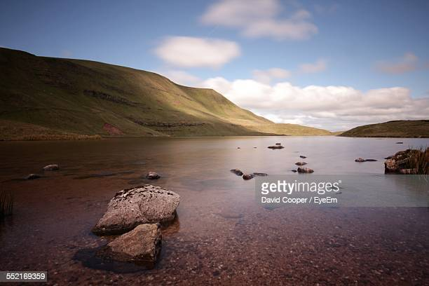 Idyllic Landscape With Hills Lake, Stones In Water, Clouds In Sky