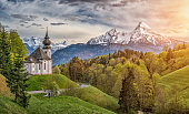 Beautiful mountain landscape in the Bavarian Alps with famous pilgrimage church of Maria Gern and Watzmann massif in golden evening light, Nationalpark Berchtesgadener Land, Bavaria, Germany