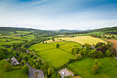 Dramatic aerial view of gently rolling patchwork farmland with pretty wooded boundaries, in the beautiful surroundings of the Cotswolds, England, UK. Stitched panoramic image.