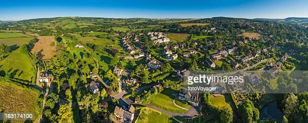 Idyllic rural village homes in green summer landscape aerial panorama