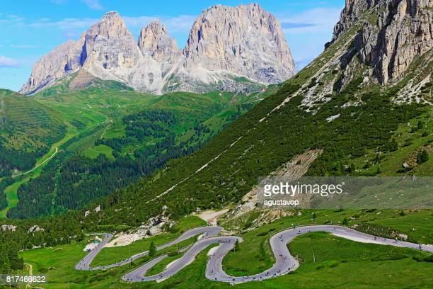 Idyllische Sas Pordoi pinnacle Winding Road, Mountain Pass und Langkofel massiv Bergkette, Wildblumen Frühling, dramatischen Panorama und majestätischen Dolomiten, Italien Tirol Alpen