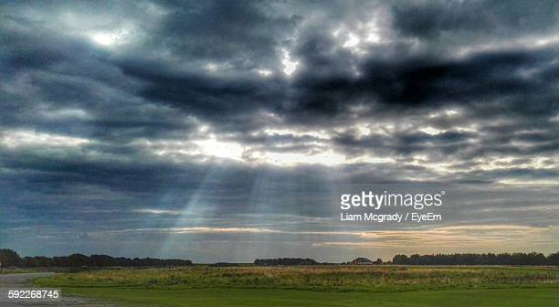 Idyllic Shot Of Sunbeam On Green Landscape Against Cloudy Sky